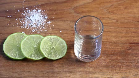 sůl : Pouring tequila in glass with lime slices and salt