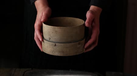 Sieving whole wheat flour through old sieve by womans hands. Dark rustic style
