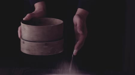 Sieving whole wheat flour through old sieve by womans hands. Dark rustic style. In retro filter effect. Stok Video