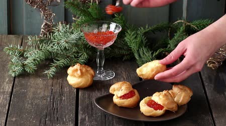 Plate with Home made Profiteroles stuffed by red caviar with glass vase of red caviar and Christmas tree at background over old wooden table. Dark rustic style.