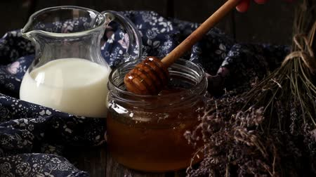 Open glass jar of liquid honey with honeycomb and honey dipper inside, glass jug of milk and bunch of dry lavender. Dark rustic style. Stok Video