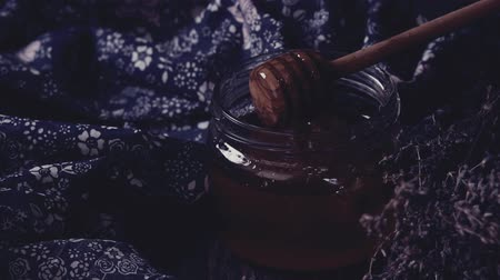 Open glass jar of liquid honey with honeycomb and honey dipper inside, bunch of dry lavender. Dark rustic style. In retro filter effect. Stok Video