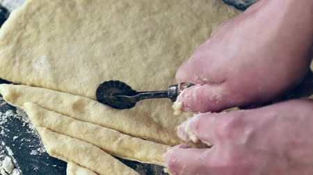 Female hands slicing dough for pasta by vintage roll over black table, powdering by flour