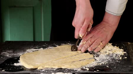 Female hands making dough for pasta over black table