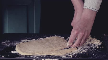 Female hands slicing dough for pasta by vintage roll over black table, powdering by flour. Dark rustic style. In retro filter effect Stok Video