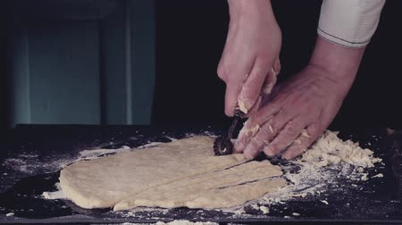 Female hands making dough for pasta over black table. Dark rustic style. In retro filter effect Stok Video