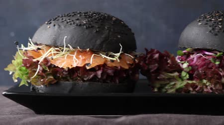 Two homemade black burgers with salted salmon, beetroot cutlet, sprouts and green salad on black plate over dark background Stok Video