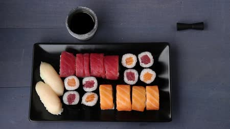 Sushi set nigiri and rolls on black plate served with chopsticks, soy sauce, wasabi and ginger. Flat lay