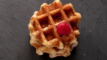 Belgian waffles with raspberries and sugar powder over rusty surface. Flat lay Stok Video