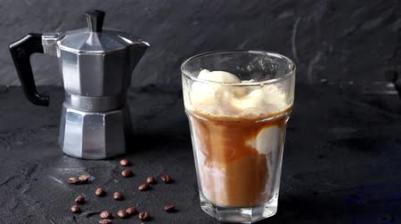 Pouring in glass with ice cream ice coffee with whipped cream and chocolate sauce, served with coffee beans over black background Stok Video