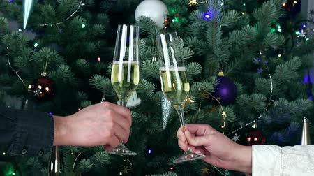Couple toasting glasses with white champagne wine by decorated illuminated Christmas tree Stok Video