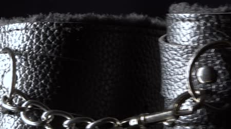 kajdanki : Closeup of black leather handcuffs moving around on the black background Wideo