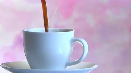 porcelana : Pouring coffee in a white cup on a pink background Stock Footage