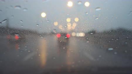 Driving on freeway and rainy in twilight, rack focus. 動画素材
