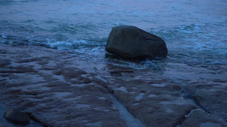 shot of rock in the ocean at dusk filmed at Australia, Queensland, Sunshine Coast, Caloundra, Kings Beach