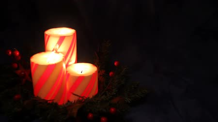three Christmas pillar candles with holly berries