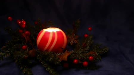 red and white striped Christmas ball candle glowing and flickering