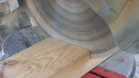 miter saw : Closeup view of a miter saw cutting a 2 by 4 board at a construction site