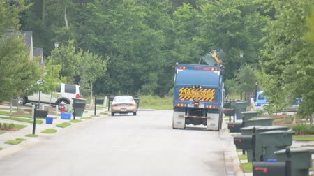 ciężarówka : automated arm picking up and dumping large green trashcan on residential street