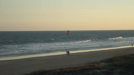 sc : couple walking and jogger with kite surfer speeding along Isle of Palms beach near Charleston SC