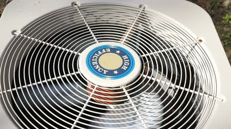 condicionador : high efficiency heat pump fan spinning providing cool house on a hot day