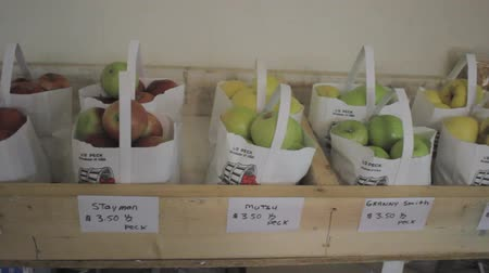 tracking of a variety of bagged mountain apples at a roadside produce market Vídeos