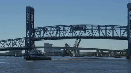 Large tugboat pulling long load with smaller tugboat at rear going under the closing drawbridge in downtown Jacksonville Florida Vídeos