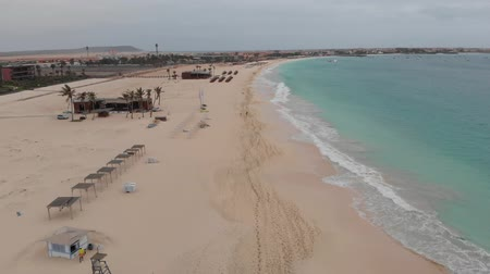 Aerial 4k footage of the beautiful beach and coastline of Cape Verde (Capo Verde) with people sunbathing on the golden sandy beach and boasts in the ocean, taken with a drone on May 2018