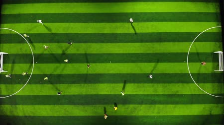 4K Aerial footage of a football pitch with players playing football on a stripy green football pitch showing the pitch and goals, this footage was taken at night with flood lights taken with a drone. Wideo