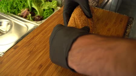 バゲット : A baguette is being cut on a wooden board in a kitchen 動画素材