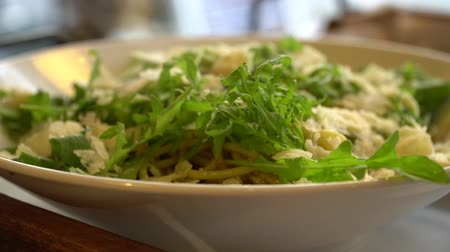 пармезан : Close up of hot spaghetti with pesto sauce, green rocket salad and parmesan cheese