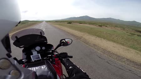 austrian : motorcyclist driving on road in steppe with mountains