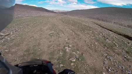 moğolistan : motorcyclist driving on road in mountains with rocks
