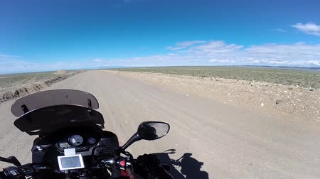 irreconhecível : motorcyclist driving in desert with mountains at horizon