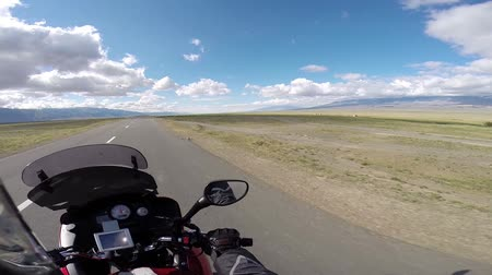 lovas : motorcyclist driving in desert with mountains at horizon