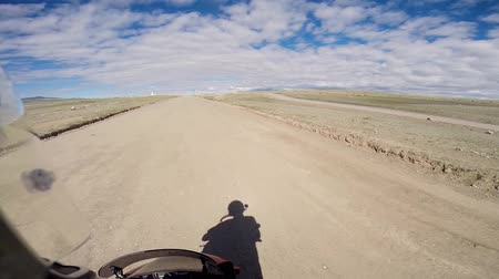 motorcyclist driving on road in steppe with mountains