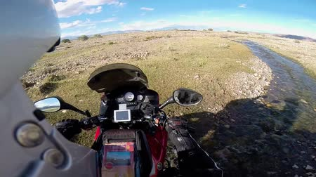 motorcyclist driving on river in mountains
