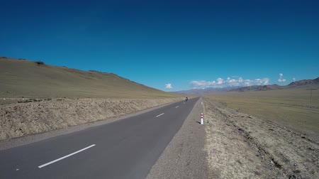 motorcyclist driving on road in mountains