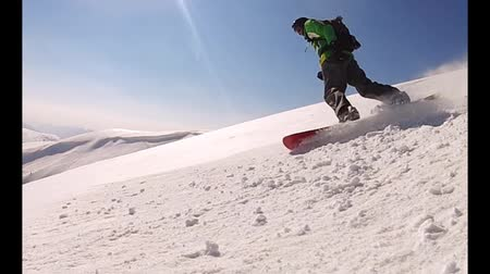 snowboard : The snowboarder is riding over the fields of a powder snow in the mountains in a slow motion. Enjoy!