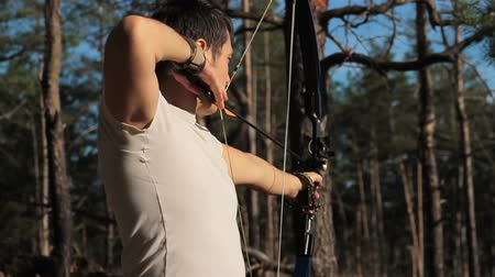 strzałki : The young man is shooting from the sports bow in a sunny forest. Wideo