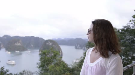 ha : young woman tourist looking far away on sea and islands background
