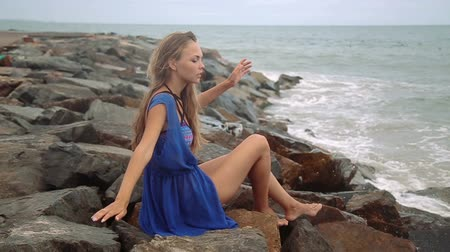 outside : Gorgeous young girl with a beautiful figure posing and walks along the seashore