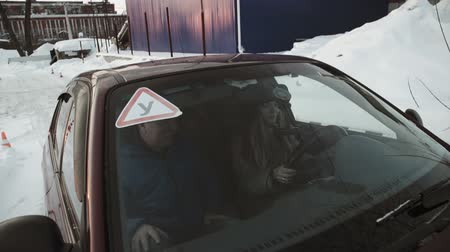 samochód : Driving instructor points out mirrors to pretty teenage girl sitting in car