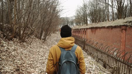 nuclear accident : A young man With backpack on back walks through the park in the spring or autumn trees yellow leaves, next to an abandoned German fort, brick walls, an old iron fence Stock Footage
