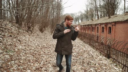 nuclear accident : A young man With a beard, in a gray coat walks through the park in the spring or autumn trees yellow leaves, next to an abandoned German fort, brick walls, an old iron fence Stock Footage