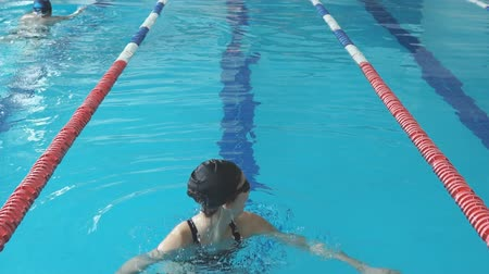 atlet : Fit swimmer girl jumping and cheering in swimming pool Stok Video