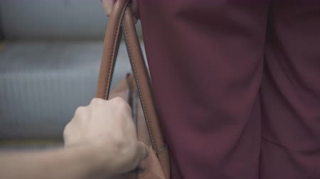 roubo : Pickpocket thief is stealing smartphone from orange handbag. Stock Footage