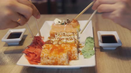 seafood dishes : People eating rolls in japan restaurant or sushi bar.