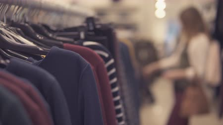 milan fashion : Girl choosing pullover clothes, blurred backgound Stock Footage