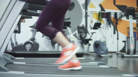 compleição : Woman running on a treadmill, close-up. 4k.